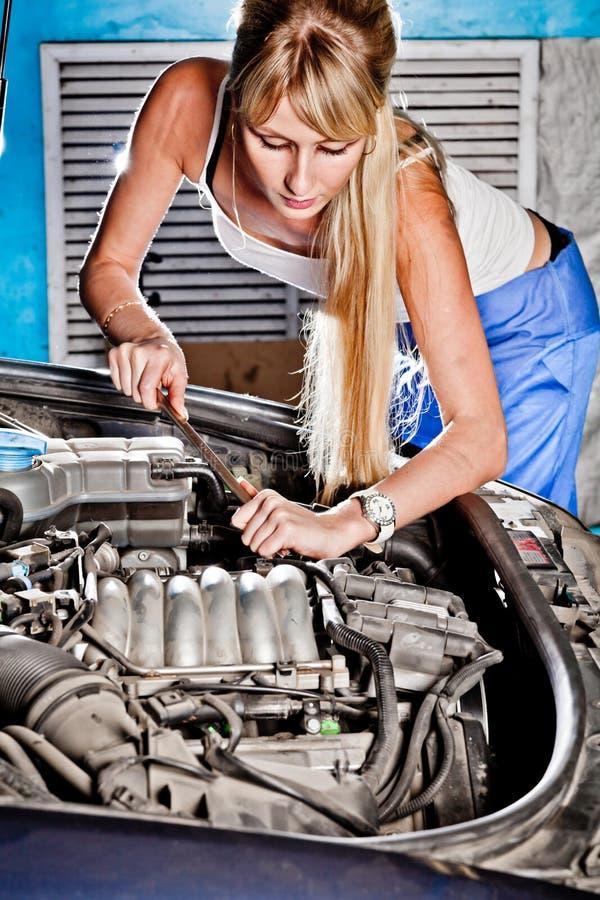 Intentos de la muchacha para reparar el coche roto fotos de archivo libres de regalías