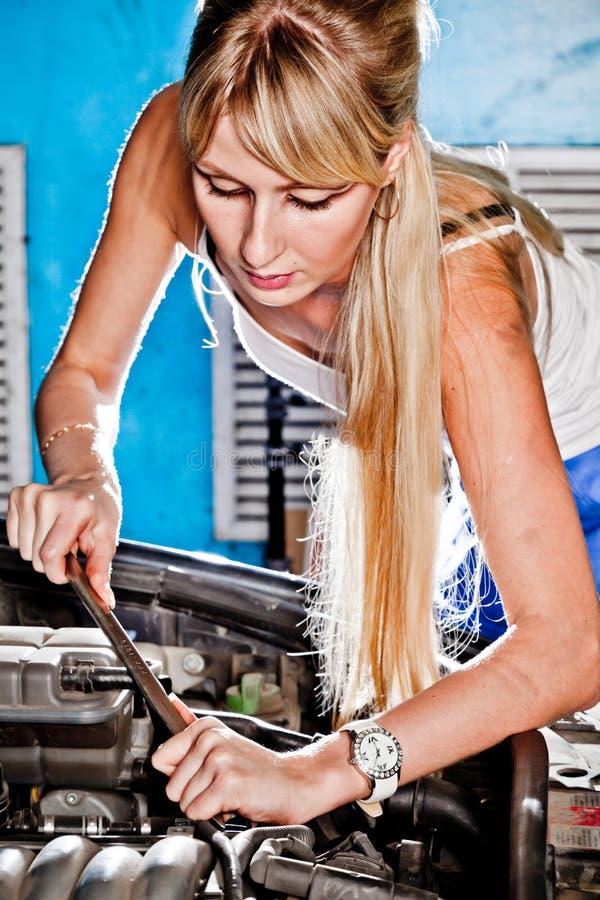 Intentos de la muchacha para reparar el coche roto imagen de archivo libre de regalías