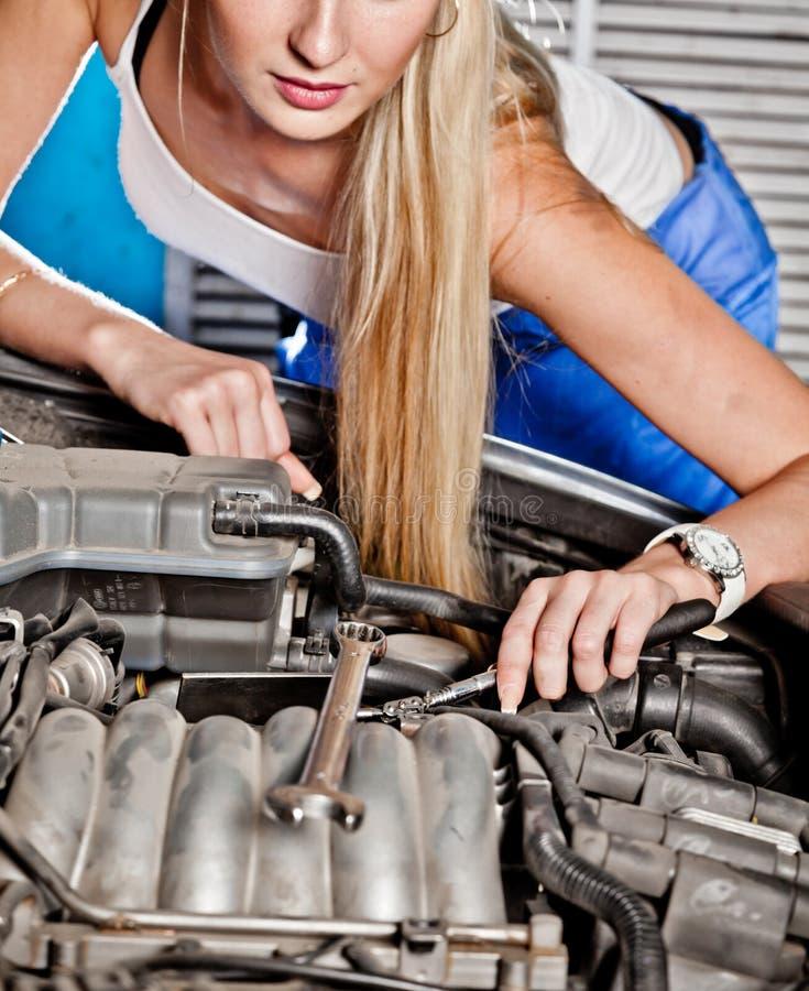 Intentos de la muchacha para reparar el coche roto fotos de archivo