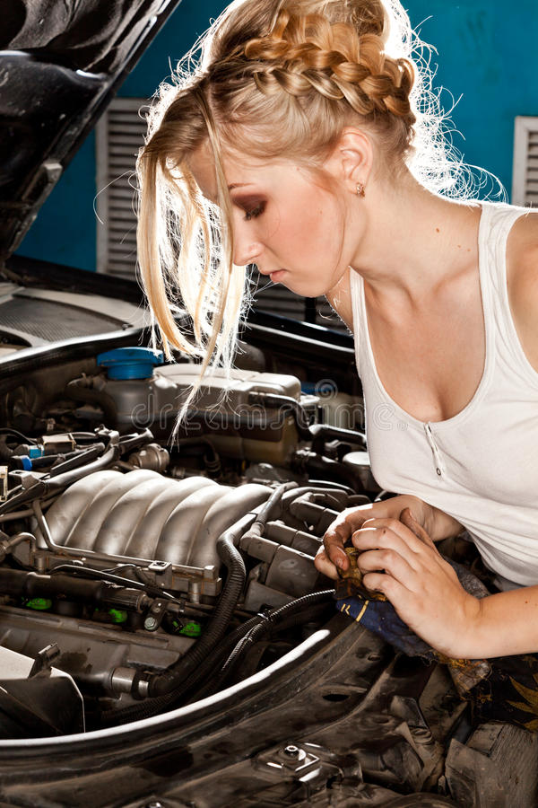 Intentos de la muchacha para reparar el coche roto imagenes de archivo