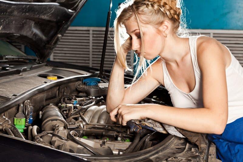 Intentos de la muchacha para reparar el coche roto fotografía de archivo