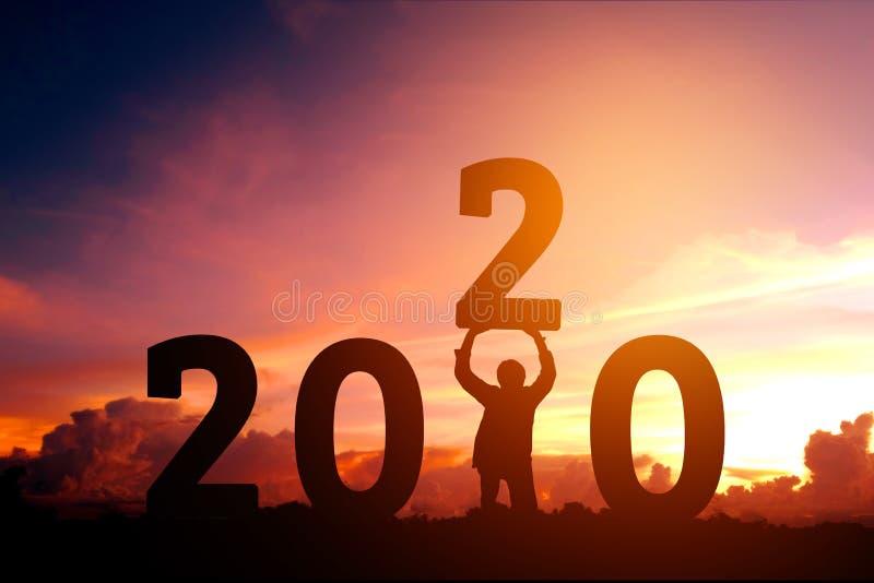Intentos 2020 del hombre de Newyear para levantar para arriba el número de concepto de la Feliz Año Nuevo 2020 fotografía de archivo