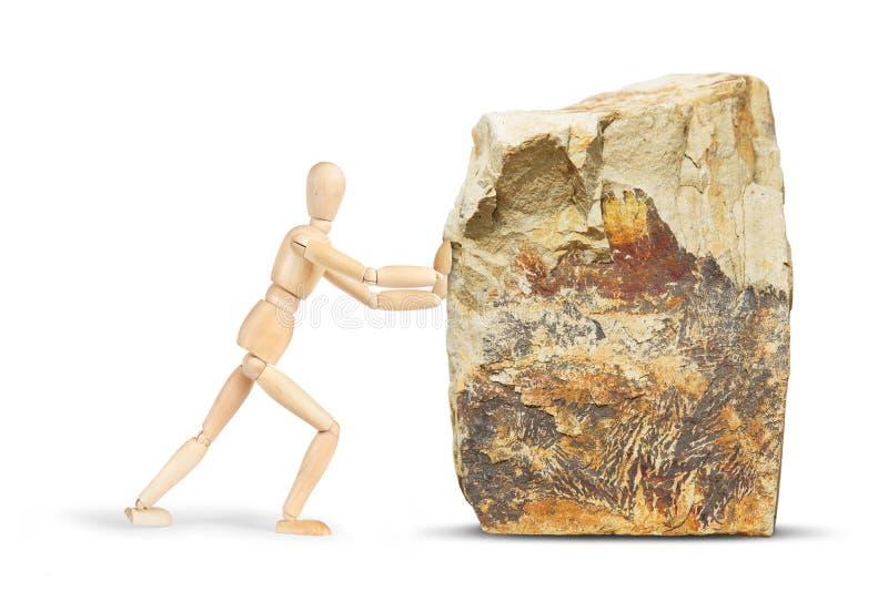Intentos del hombre para mover una roca enorme fotografía de archivo libre de regalías
