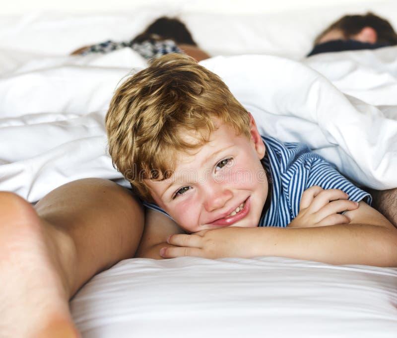 Intera famiglia che divide un letto fotografia stock libera da diritti