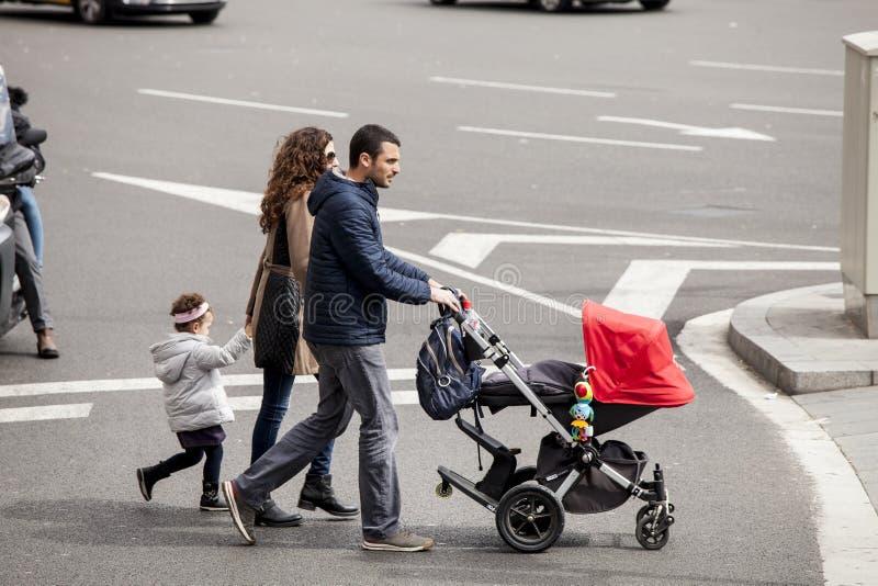 Intera famiglia con il passeggiatore che cammina sulla strada Barcellona, Spagna immagine stock