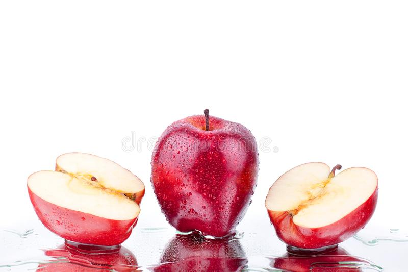 Intera mela delle mele rosse e vista laterale differente cutted sulla fine isolata fondo bianco sulla macro immagini stock
