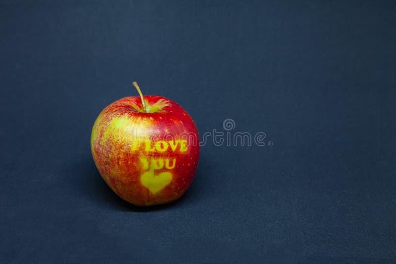 Intera mela rossa su un fondo nero con le parole ti amo fotografie stock libere da diritti