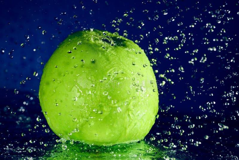 Intera mela verde con le gocce dell'acqua immagine stock