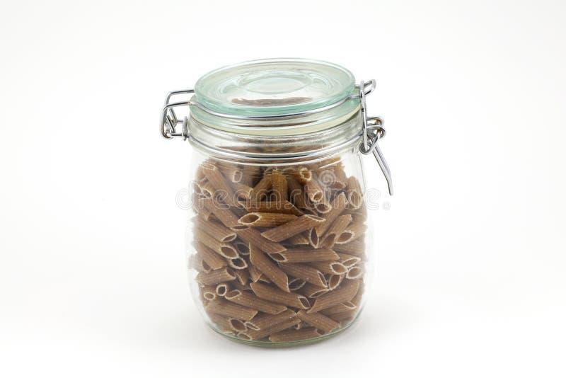 Intera pasta del granulo in un vaso su priorità bassa bianca fotografia stock