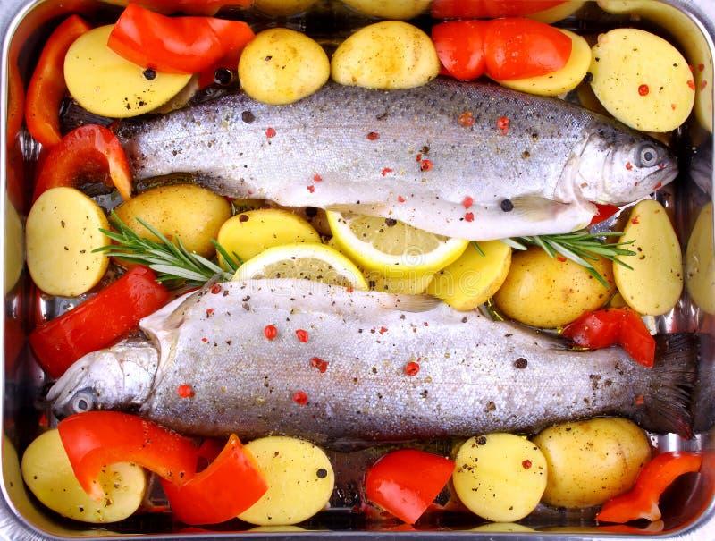 Intera trota iridea due con peperone, la patata ed il limone fotografie stock libere da diritti