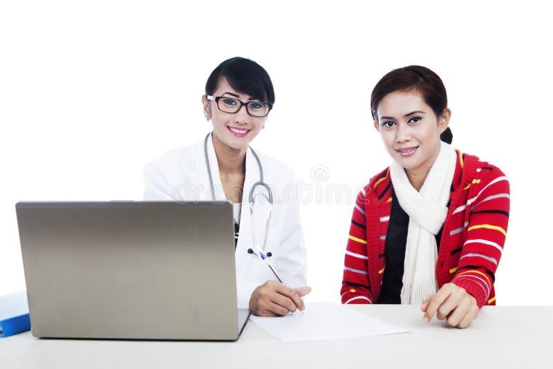 Interacción del doctor y del paciente usando la computadora portátil foto de archivo libre de regalías