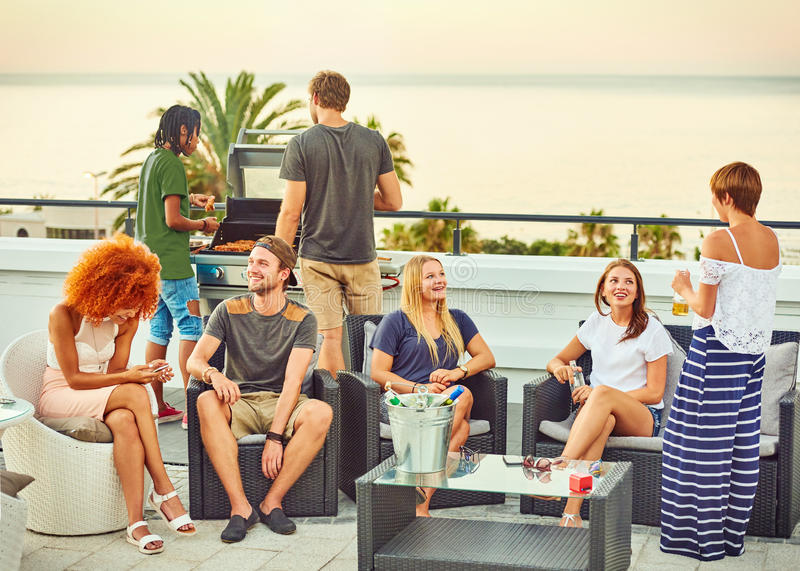 Interacción social entre un grupo atractivo de frineds durante barbacoa foto de archivo libre de regalías