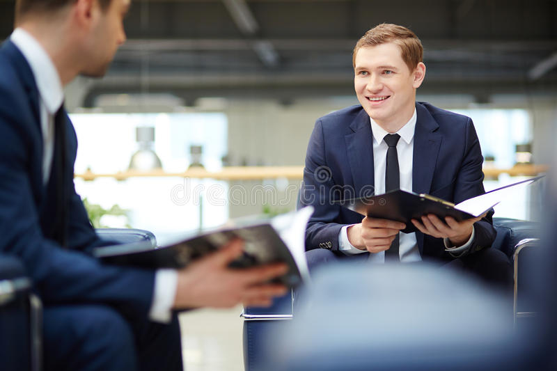 Interacting at meeting. Image of two young businessmen communicating at meeting stock image