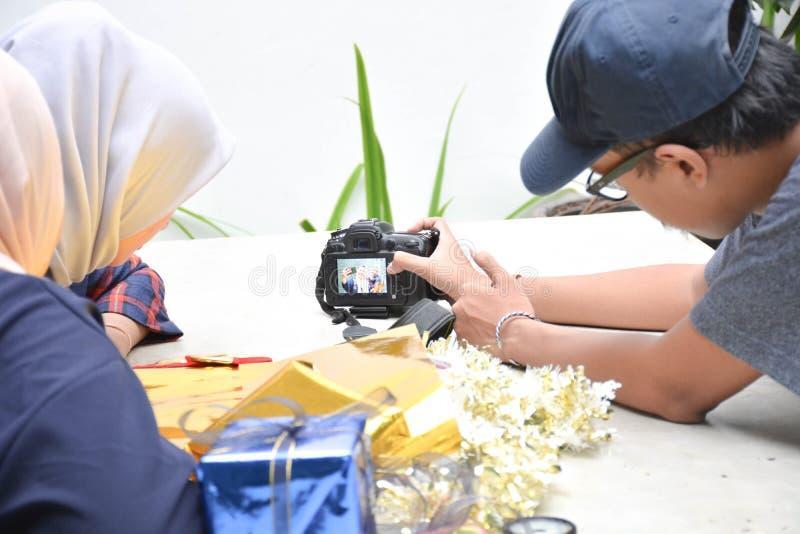 Interaction entre le photographe masculin avec le hijab deux femelle sur la table photographie stock