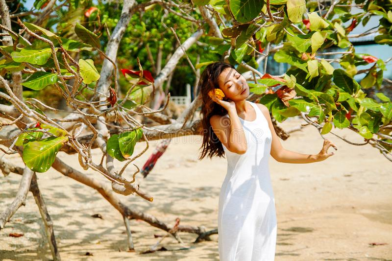 The interaction of man and nature. Beautiful asian woman on the beach. royalty free stock image