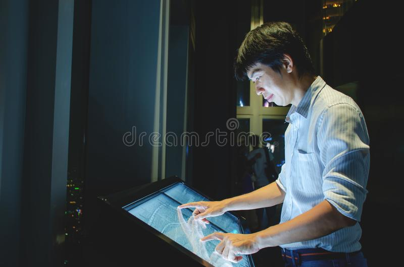 Interactive kiosk with public transport large building map.Hand of a man pointing finger and touching to screen large display. While consults about touristic stock photography