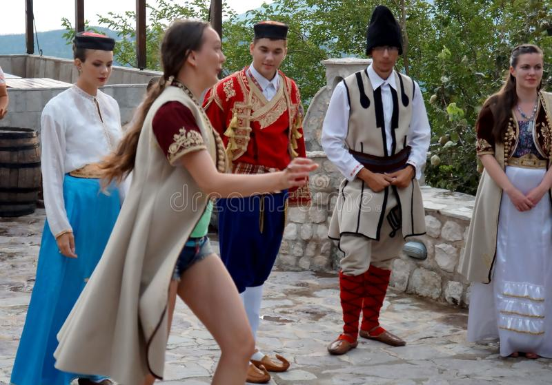 Interactive moment. One girl from Latvia trying to dance with beautiful dancers and singers at the nice folk style evening meal in Montenegro royalty free stock photos