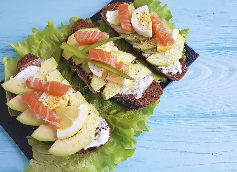 Intercale el aperitivo de madera azul gastrónomo de peces del aguacate de los huevos del limón rojo del almuerzo rústico imagen de archivo