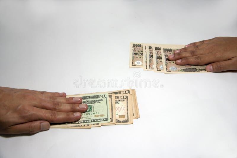 Intercambie el concepto del dinero, mano en los billetes de banco de los E.E.U.U. cambian con la mano en los billetes de banco ja imagenes de archivo