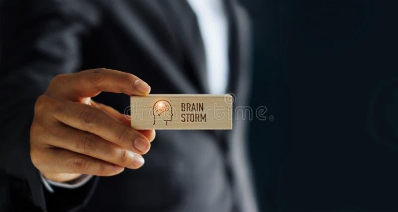 Intercambio de ideas de la palabra del icono de la tenencia del hombre de negocios en bloque de madera imagen de archivo libre de regalías