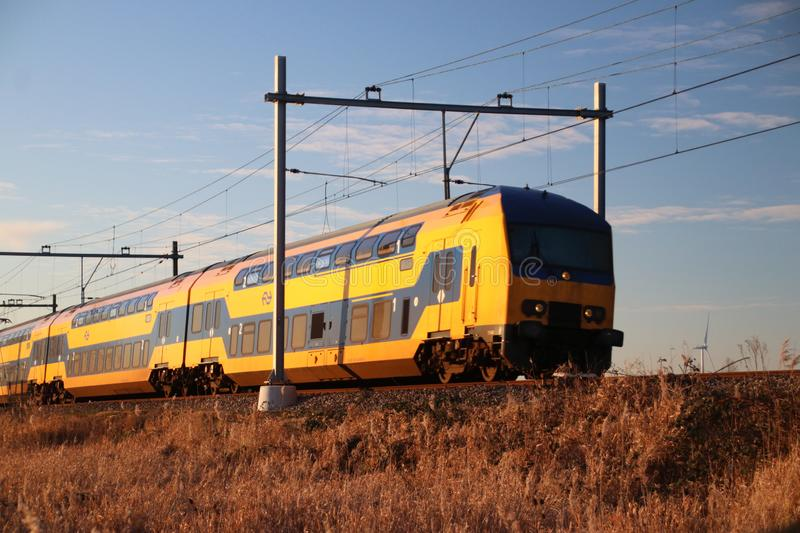 Intercity train type DDZ of the NS at Moordrecht in evening sun between Den Haag and Gouda. stock image