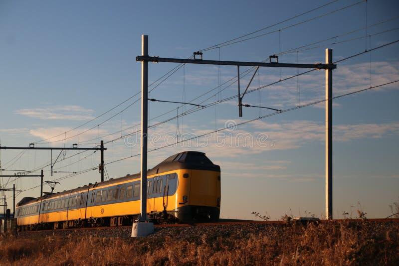 Intercity train type ICM Koploper of the NS at Moordrecht in evening sun between Den Haag and Gouda. stock photo