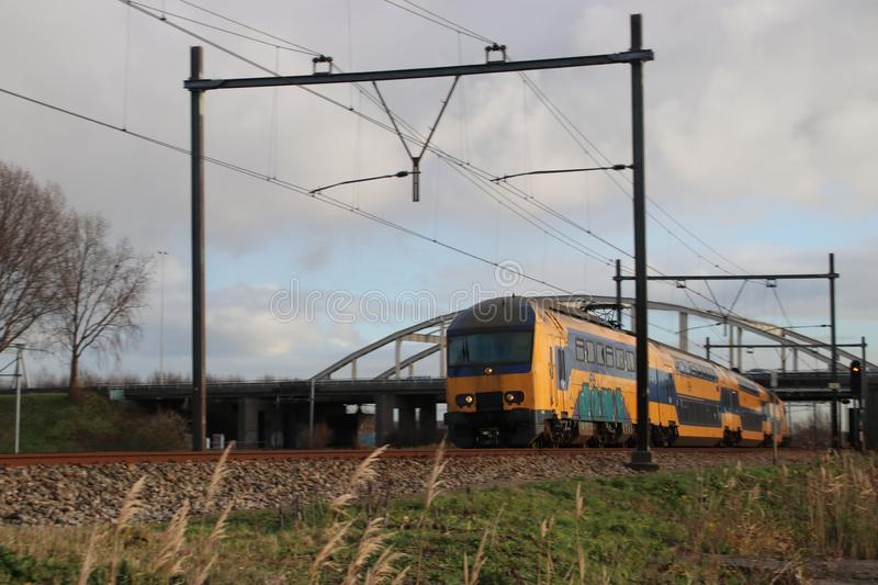 Intercity train type SGM double decker at railroad track between Gouda and The Hague at Moordrecht crossing. stock photos