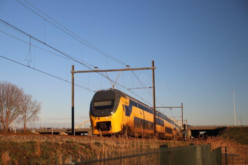 Intercity train type VIRM of the NS at Moordrecht in evening sun between Den Haag and Gouda. stock photos