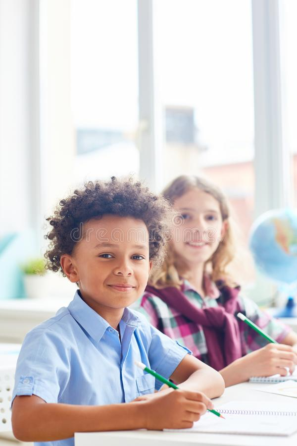 Intercultural schoolboys. Intercultural boys sitting by desk at lesson of drawing royalty free stock photography