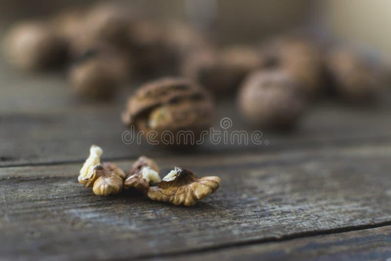 Intere e noci tagliate sulla tavola di legno immagini stock