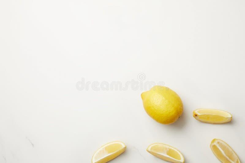 Intere frutta matura e fette gialle di limone isolate su bianco immagini stock libere da diritti