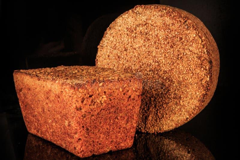 intere pagnotte del primo piano due del pane del cereale con i semi di sesamo fotografia stock libera da diritti