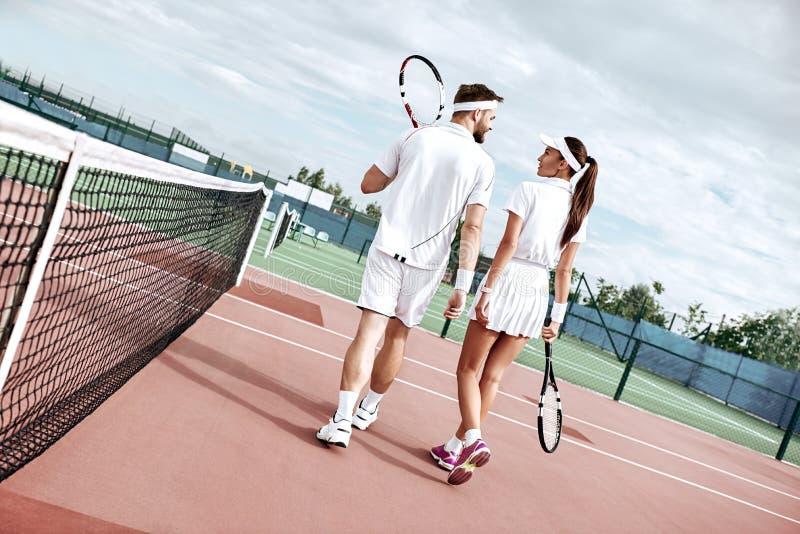 Intereses comunes El par joven va a jugar a tenis en la corte foto de archivo libre de regalías