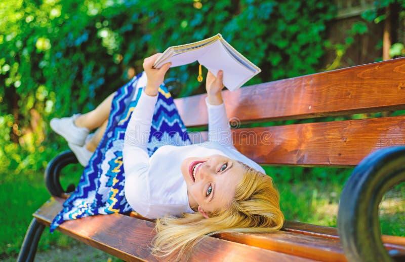 Interessant boek Dame het glimlachen het gezicht geniet rust in openlucht Meisjes van lezing terwijl het ontspannen op bank Het m stock fotografie