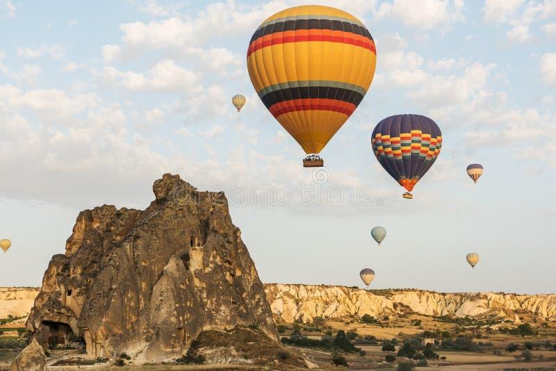 Interessant rotsachtig terrein en heel wat luchtige multicolored ballen in de lucht Turkije stock afbeeldingen