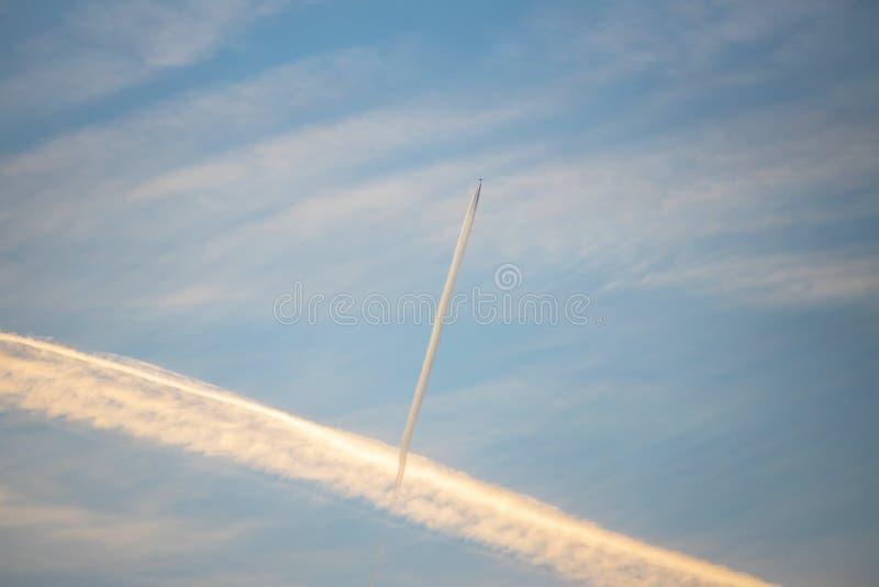 Interessante lange strook van condensatie in de lucht vliegtuigcontra stock foto's
