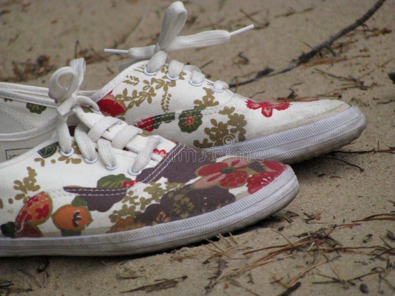 Interessante schoenen op de zandige grond stock afbeelding