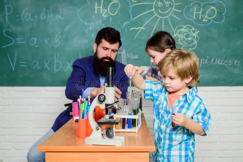 Interessante schoolklassen Schoolonderwijs Het experiment van de schoolchemie Schoolclub Het verklaren van chemie aan jong geitje royalty-vrije stock foto's