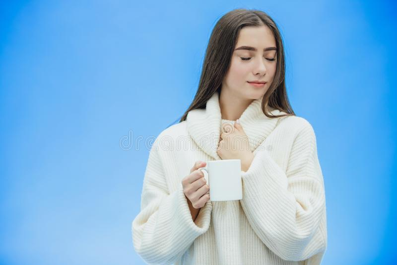 Interessantemente, uma jovem mulher em uma camiseta branca feita malha Guarda uma xícara de café ou um chá branco em suas mãos Is fotografia de stock royalty free