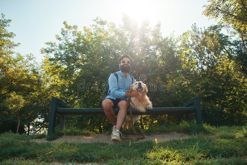 Interessanter Mann, der mit seinem Hund auf dem Stuhl im Parken sitzt lizenzfreie stockfotografie