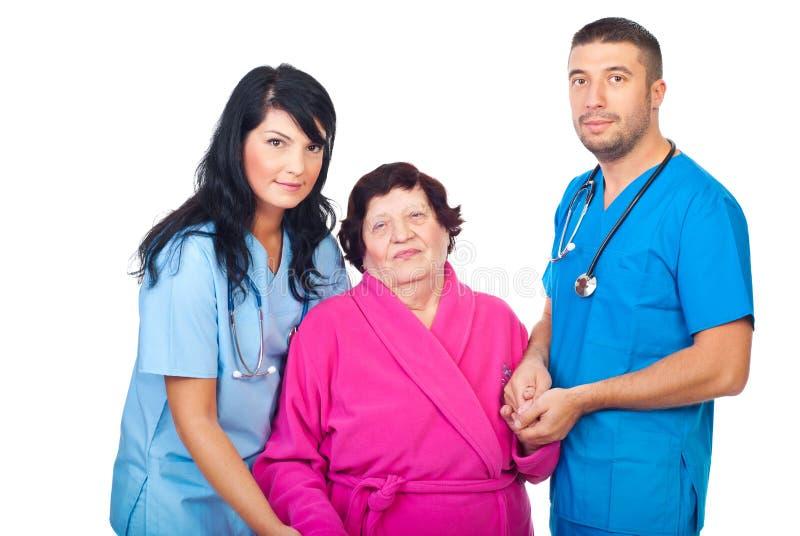 Interessierende Doktoren mit älterem Patienten stockfotografie