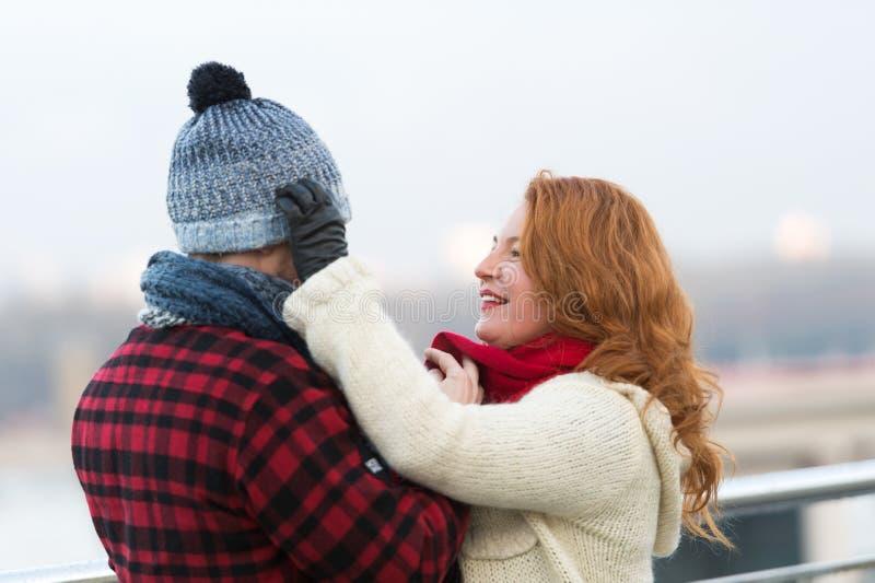 Interessierende Frau, die warmen Hut auf ihren Ehemann setzt stockfotos