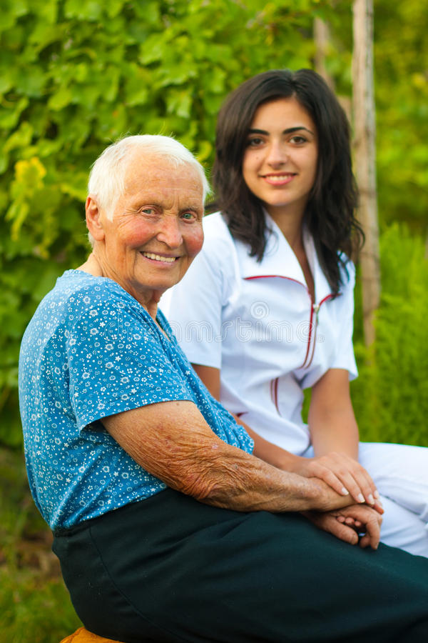 Interessierender Doktor mit kranker älterer Frau draußen lizenzfreie stockfotos