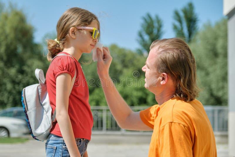 Interessierender Vati hilft seinem Kind, abwischt seine Lippen, die mit Eiscreme beschmutzt werden stockbilder