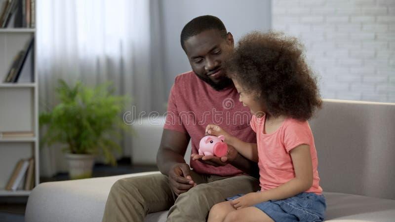 Interessierendes Vaterunterrichtskind, zum des Geldes, Mädchen zu sparen, das Münzen in Sparschwein setzt stockbilder