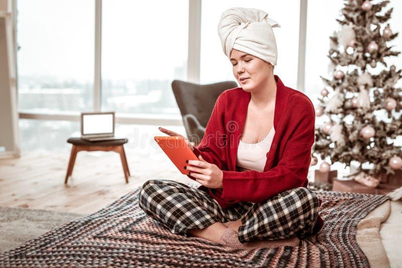 Interessierte beruhigende Frau im Hauptkostüm, das auf Bett mit Tablette sitzt stockbild