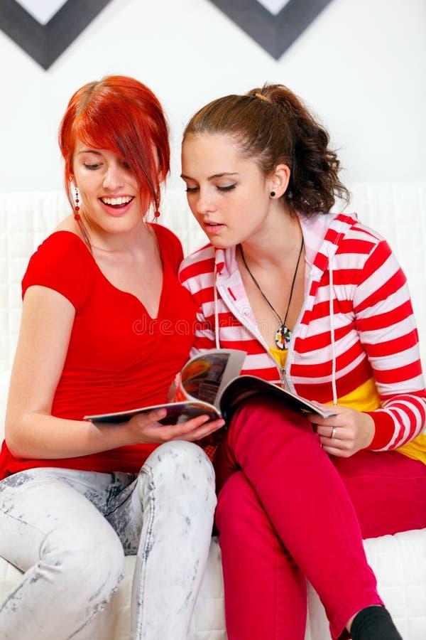 Interessierte junge Freundinnen, die Zeitschrift schauen stockfotos