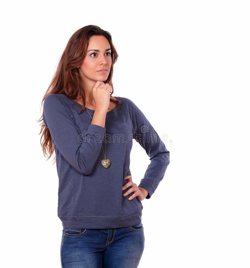 Interessierte lateinische junge Frau, die sich allein reflektiert stockbilder