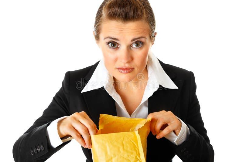 Interessierte moderne Geschäftsfrau, die Paket überprüft stockfotografie