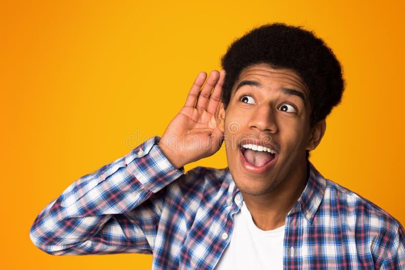 Interessierter Kerl, der versucht, die Informationen, Hand nahe Ohr halten zu hören lizenzfreie stockfotos